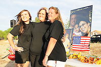 "Gilbert, Arizona – Friends and family of the Mederos Family gathered to hold a memorial for the four victims of the Gilbert Massacre occurred on May 2, 2012. According to Gilbert Police, Lisa Mederos, Amber Mederos, baby Lilly Mederos, and Jim Hiott (Amber's fiancé) were all killed by notorious white supremacist and Neo-Nazi Jason ""J.T."" Ready before taking his own life. In this image, Whitney Byrd, Crystal Seibert and Mistie Whiteman are photographed by a friend next to a memorial table with flowers and photos of the four victims killed. Photo by Eduardo Barraza © 2012"
