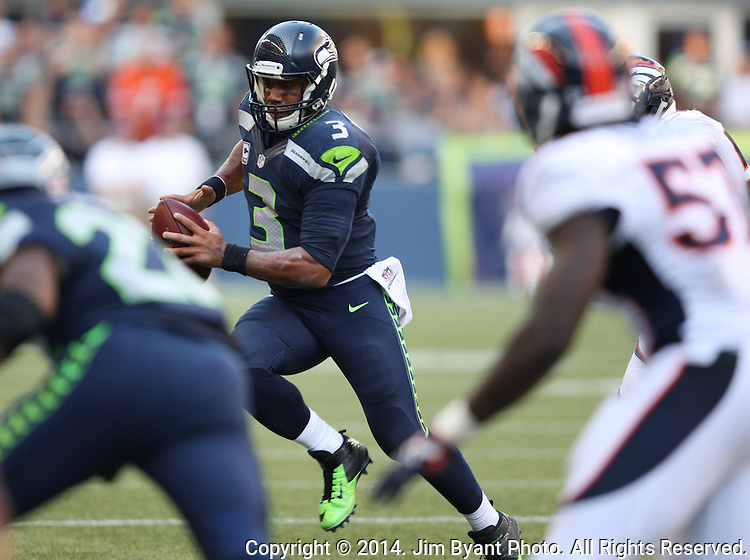 Seattle Seahawks quarter Russell Wilson (3) scrambles away from the Denver Broncos  at CenturyLink Field in Seattle, Washington on September 21, 2014.  Wilson completed 24 of 34 passes for 258 yards, two touchdowns and one interception in the 26-20 overtime win against the Broncos.  ©2014. Jim Bryant Photo. All rights Reserved.
