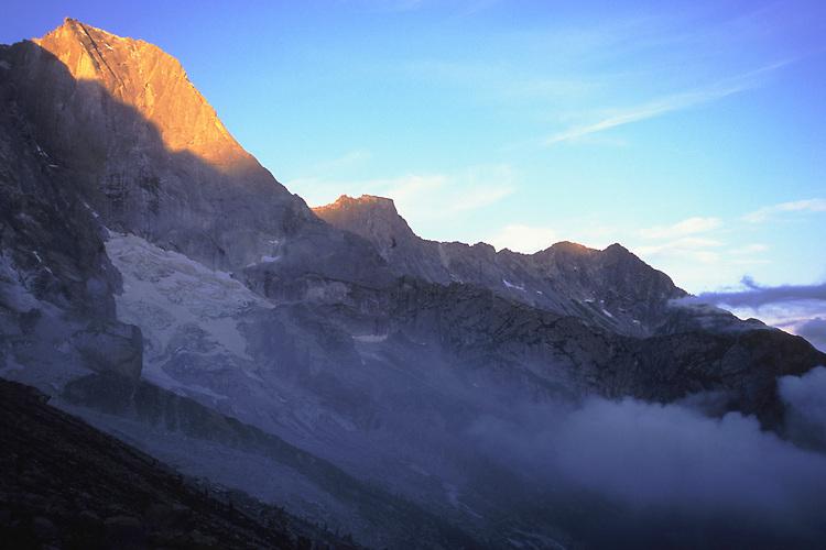 Pizzo Badile (3303 m) and Pizzo Trubinasca (2918 m) emerge from the morning mist, Bergell, Switzerland, August 2011.