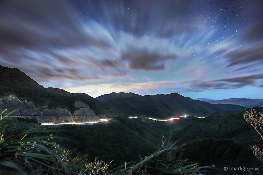Cars make their way up State Highway 2 over the Rimutaka Hill just out of the city of Wellington, New Zealand. The moon had just risen this night, lighting up the surrounding landscape. The lights from the cars created light trails along the road during the 30 second exposure.