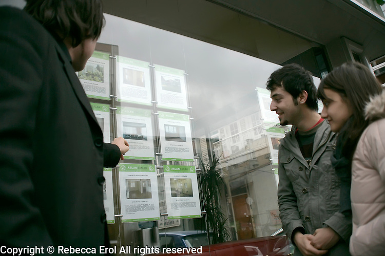 Young couple look in the window of an estate agent, Istanbul, Turkey