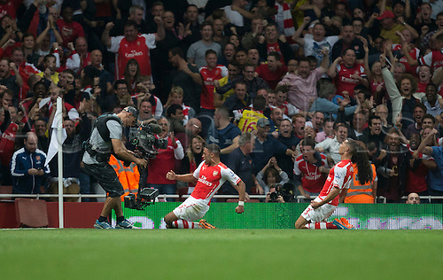 27.09.2014.  London, England. Barclays Premier League. Arsenal versus Tottenham Hotspur. Arsenal's Alex Oxlade-Chamberlain slides on his knees in celebration of his equalising goal.