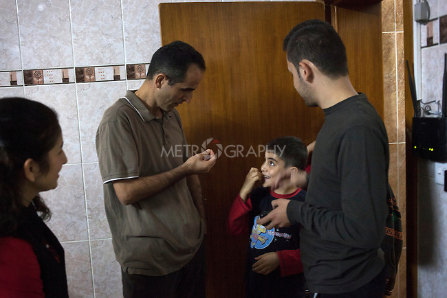 """21/10/14. Erbil, Iraq. Milad and Wassam's uncle Salam (left) prepares to take the brothers out for a walk to buy snacks. Milad (centre) is impatient, Salam says, """"My son, I said we are going in a minute, slow down!"""""""