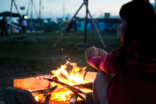 Charlotte from France is getting some warmth from the campfire. Photo: Fredrik Sahlström/Scouterna
