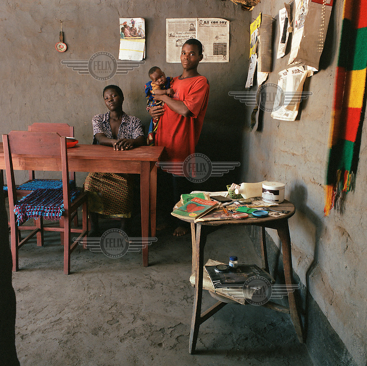 Aron Thunde (23) with his wife Lamesi and baby son Bestar next to their dining table in their house.  Aron is one of the only villagers to have finished secondary school and wants to be a teacher.