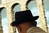 An old man looking at the Segovia Aqueduct