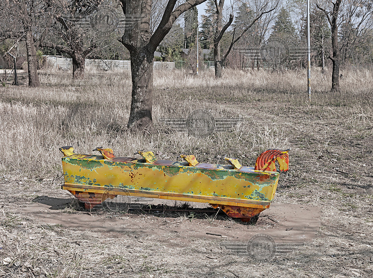 A children's playground toy sits in a neat patch of land.  Graeme Williams' pictures of the environments occupied by some of South Africa's poorest people focus on the interiors and exteriors of people's homes, accentuating the minutiae of the occupants' day-to-day dwelling places. The bright colours captured in these photographs are suggestive of resilience, hope and a sense of humanity that survives in these poverty-stricken communities...