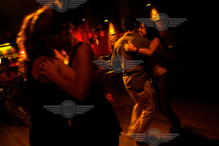 Ceci and Meme tango dance at a milonga in Buenos Aires. They are dancing partners and work at a restaurant in the El Caminito area. Their passion for dancing is so great they go out to milongas even after dancing for many hours at the restaurant.