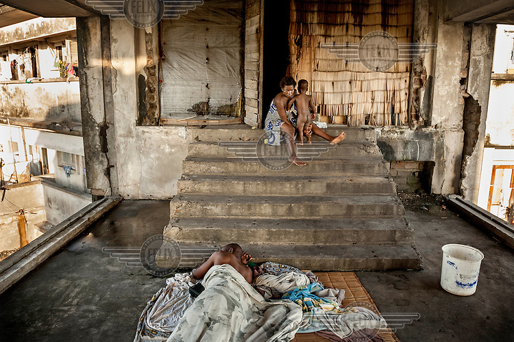 A woman washes her child while a man sleeps at the base of some concrete steps in the former Grand Hotel building. Once a luxury destination for the wealthy and the continent's biggest hotel, the building is now a concrete shell and home to about 6,000 squatters. Those unable to occupy one of the rooms sleep in the corridors, basements and even on the roof of the building.
