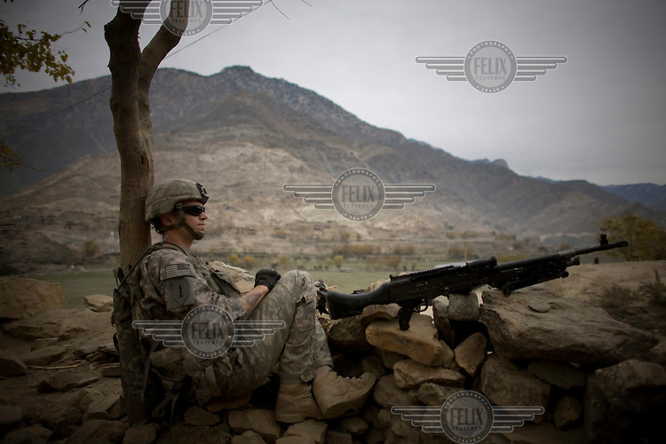 A soldier from 3rd Platoon, Charlie Company, 1-26 Infantry on lookout during a meeting with village elders.