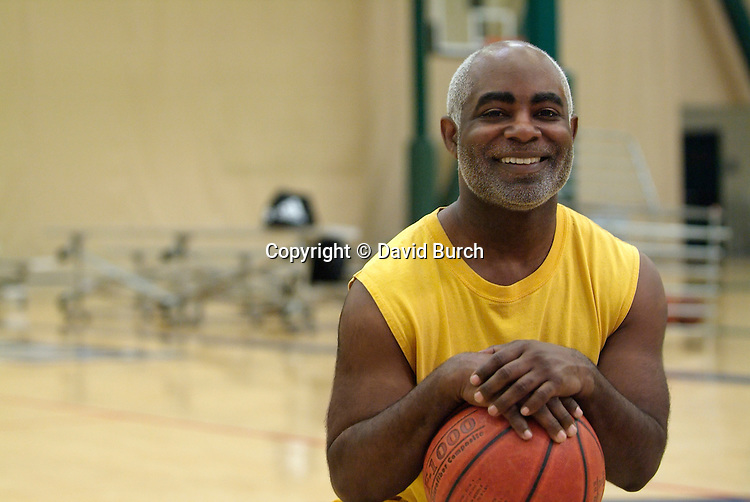 African American man holding basket ball and smiling