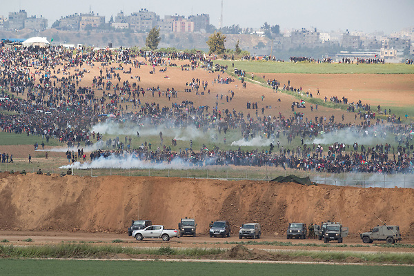 A picture taken on March 30, 2018 from the southern Israeli kibbutz of Nahal Oz across the border from the Gaza strip shows tear gas grenades falling during a Palestinian tent city protest commemorating Land Day, with Israeli soldiers seen below in the foreground. Land Day marks the killing of six Arab Israelis during 1976 demonstrations against Israeli confiscations of Arab land. Photo by: JINIPIX