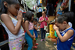 Deaconess Irene Lagahit Vioya leads a group of children in prayer in a neighborhood in Manila, Philippines. A graduate of Harris Memorial College, she works on the staff of Knox United Methodist Church.