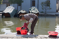 A villager does her laundry at a canal in Zhouzhuang Town of Jiangsu Province, China on November 18, 2008. Zhouzhuang, one of the most famous water townships in China, is noted for its profound cultural background, the well preserved ancient residential houses, the elegant watery views and the colourful local traditions and folklore. Sixty percent of the Zhouzhuang's structures were built during the Ming and Qing Dynasties from 1368 to 1911.