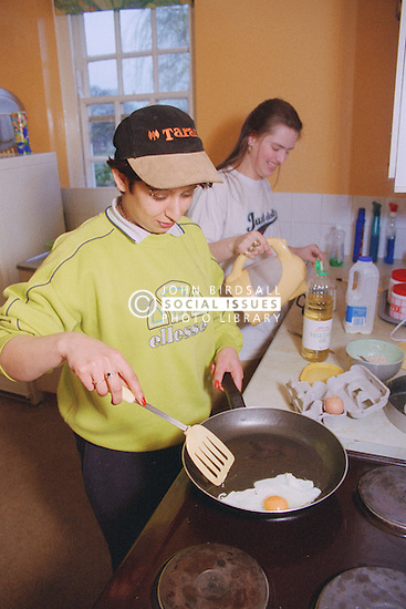Two residents preparing breakfast in communal kitchen of women only homeless hostel,
