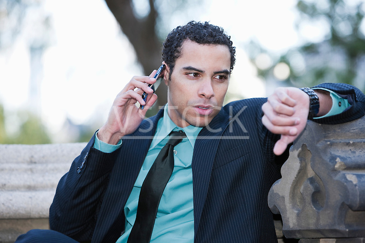 USA, New York, New York City, Businessman with cell phone checking watch