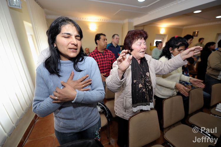 Women pray during a worship service of the United Methodist Roma congregation in Jabuka, Serbia..
