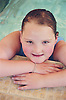Portrait of young girl with complex congenital heart disease resting on side of public swimming pool,
