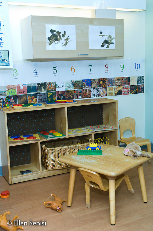 Washington, DC. Hoya Kids Learning Center at Georgetown University (private day care center for toddlers and preschoolers). ID: AI-gPhk. Pre-school classroom environment which includes shelves for puzzles, pictures to encourage language development, and numbers posted on the wall. © Ellen B. Senisi
