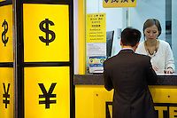 HONG KONG, MARCH 18: A person exchanges money at a currency exchange booth showing symbols of the Hong Kong dollar and the Chinese yuan, on March 18, 2015, in Hong Kong. (Photo by Lucas Schifres/Pictobank)