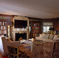 The central flatscreen TV in the drawing room is incorporated into the mantelpiece with three sofas grouped around a coffee table