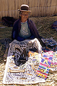 Lake Titicaca, Peru. Old woman showing souvenir embroidered cloth in a village on the floating island of Uros.