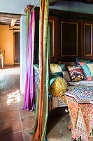 An intimate sitting area is concealed behind pretty coloured curtains. Traditional local materials were kept during the restoration of the house, such as the terracotta tiles on the floor and ceilings and the original massive wooden beams.