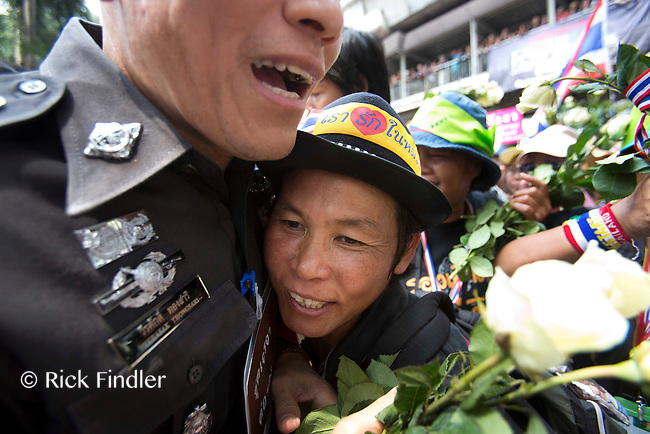 26.02.14 Anti-government protesters present flowers and hug police officers as they gathered in thousands outside the national police headquaters in Bangkok today - urging them to stop serving the regime of interim Prime Minister Yingluck Shinawatra and to join their movement. The anti-government protest leader Suthep Thaugsuban and other leading figures from the People's Democratic Reform Committee spoke from the roof of a truck and led anti-government cheers for hours.