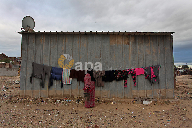 A Palestinian woman hangs laundry on a rope to dry outside her dwelling in Khan Younis in the southern Gaza Strip December 19, 2016. Photo by Ashraf Amra