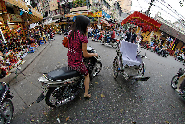 Asia, Vietnam, Hanoi. Hanoi old quarter. Elegant vietnamese woman on motorbike.