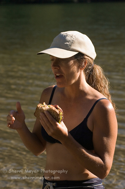 Woman eating lunch in Lake Clementine on a hot summer day, Auburn California