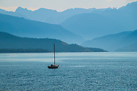 A lone sailboat sits on Grand Lake in Colorado as layers of mountains rise behind.