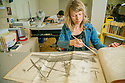 Erin Hammeke, senior conservator for special collections, works with a French encyclopedia of 18th Century technologies, like shipbuilding, typesetting, and farriering in The Verne and Tanya Roberts Conservation Laboratory in Perkins Library.