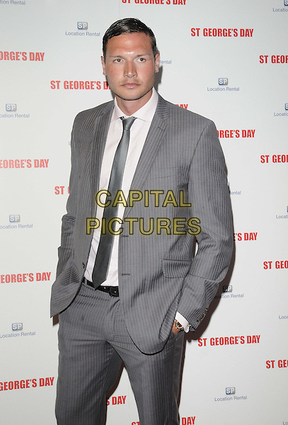 guest.The 'St George's Day' world film premiere, Odeon Covent Garden cinema, Shaftesbury Avenue, London, England..August 29th, 2012.half length white shirt tie grey gray suit jacket hand in pocket .CAP/CAN.©Can Nguyen/Capital Pictures.