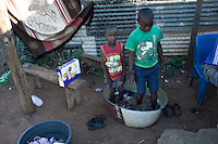 KHUTSONG, SOUTH AFRICA - OCTOBER 16: Children wash clothes  on October 16, 2012, in Khutsong, South Africa. Khutsong, a black township. is located about 56 miles west of Johannesburg, and surrounded by gold mines. Because of recent strikes many mineworkers has been fired which is making the poverty worse here. (Photo by Per-Anders Pettersson)