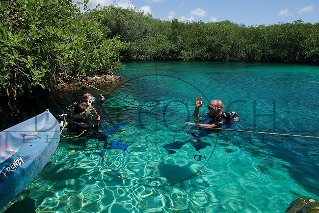 A dive master teaching scuba diving to students in a cenote near Tulum, Mexico