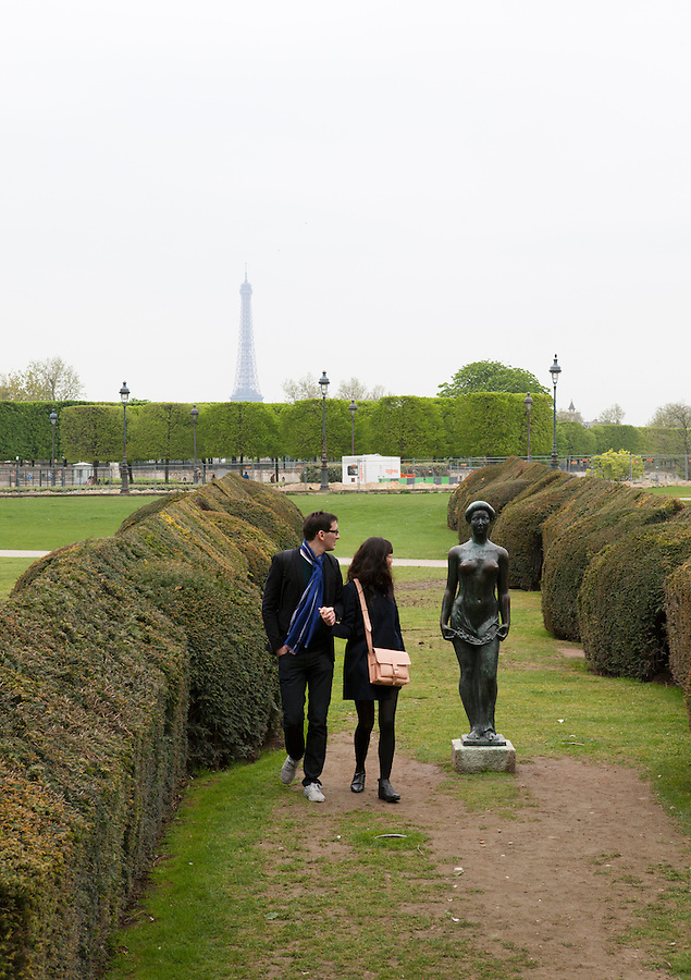 """A couple walks by """"Flora,"""" a statue by ARISTIDE MAILLOL, (1911), Tuileries Gardens (Jardin des Tuileries) in spring, Paris, France, Europe"""