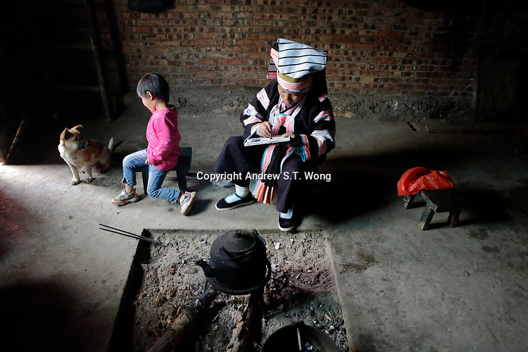 A woman of the ethnic Bouyei Tribe draws with liquid wax as she does batik at home at Wangmo County in China's southwestern Guizhou Province, April 2019.