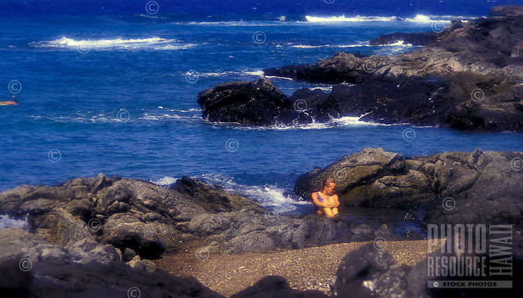Woman sitting on rocks at oceans egde looking in the water at Kona village resort on the Big island of Hawaii
