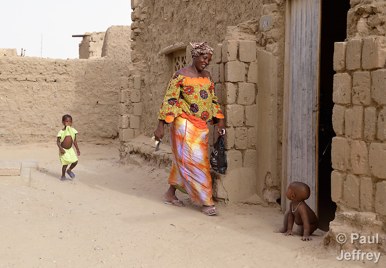 Followed by one child, a woman greets another along a street in Timbuktu, the northern Mali city that was seized by Islamist fighters in 2012 and then liberated by French and Malian soldiers in early 2013.