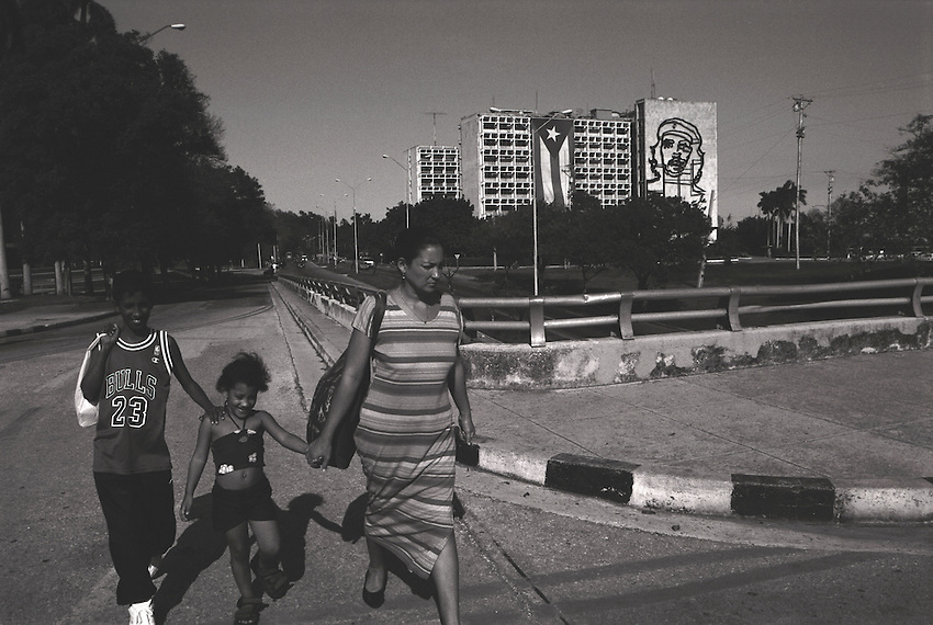 A Cuban family walks along a residential street in Havana.  In the middle distance, a tall building building is adorned with the image of Che Guevera flanked by an enormous Cuban flag.
