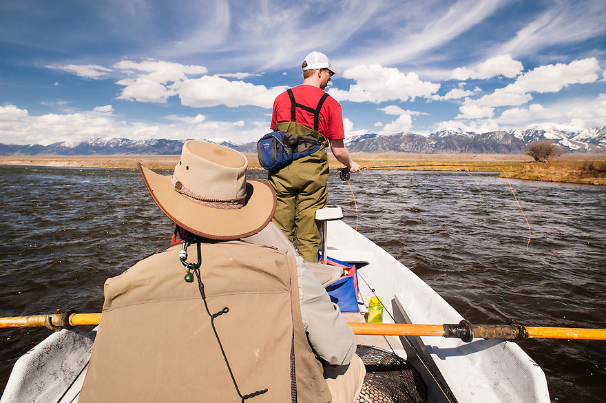 An angler fishes from the front of a drift boat on the Madison River near Ennis, Montana.