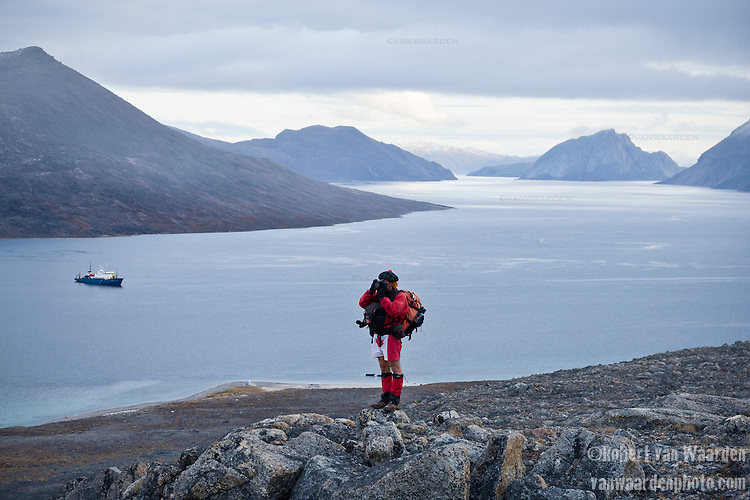 A photographer with maple leaf shorts capturing the landscape of Northern Canada. In the backgrond rests an Arctic expedition ship. Location, near Qikiqtarjuaq, Nunavut, Baffin Island, Canada.