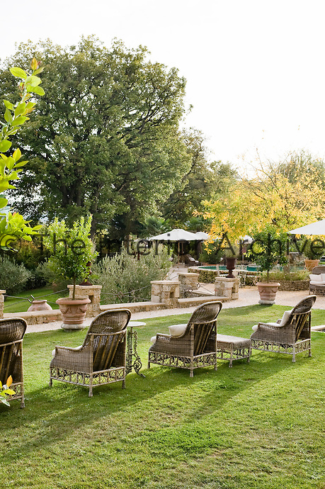 A row of wicker armchairs is placed on the manicured lawn of the hotel Borgo Santo Pietro in Tuscany
