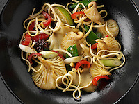Yellow Oyster mushroom stir fry being cooked with noodles, mange tout, red pepper, spring onions and start anise