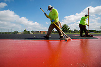 NWA Democrat-Gazette/JASON IVESTER<br /> Benito Garcia (left) and his son Cesar Garcia, both with Beynon Sports Surfaces, spread paint Monday, June 12, 2017, on the track surface at the Tiger Athletic Complex for Bentonville High School. The resurfacing project, which started about a week and a half ago, is expected to take a total of three weeks to complete.