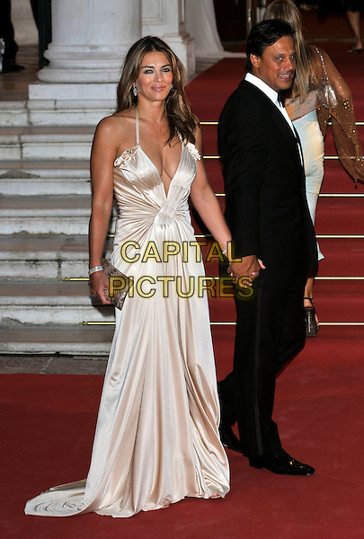 "ELIZABETH HURLEY, ARUN NAYAR.""Valentino: The Last Emperor"" screening at the Gran Teatro de Fenice during the .65th Venice Film Festival, Venice, .Italy 28th August 2008. .full length Liz gold dress  cream plunging neckline silk satin cleavage halterneck pleats gathered long maxi clutch bag black tuxedo suit married couple husband wife holding hands bow tie .CAP/PL.© Phil Loftus/Capital Pictures"