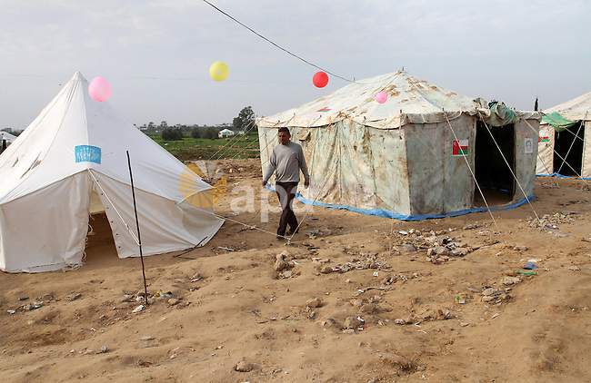 A Palestinian man, whose house was destroyed by what witnesses said was Israel shelling during a 50-day conflict last summer, walks outside his tent east of Khan Younis in the southern Gaza Strip January 27, 2015. The main U.N. aid agency in the Gaza Strip said on Tuesday a lack of international funding had forced it to suspend payments to tens of thousands of Palestinians for repairs to homes damaged in last summer's war. Robert Turner, Gaza director of operations for the United Nations Relief and Works Agency (UNRWA), said in a statement that UNRWA received only $135 million of the $720 million pledged by donors to its cash assistance program for 96,000 refugee families whose homes were damaged or destroyed in the 50-day conflict between the Hamas Islamist movement and Israel. Photo by Abed Rahim Khatib