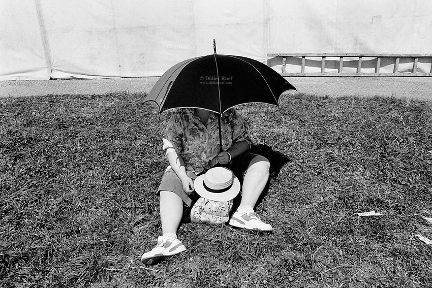"Switzerland. Canton Jura. Saignelégier. A woman, seated on the grass, protects herself from the sun by covering her face and chest with an umbrella during the traditional ""Marché-Concours"", which is one of the main Swiss horse events. The horse competition market in Saignelégier is held annually, on the 2nd weekend of August. Saignelégier is also the seat of the district of Franches-Montagnes. © 1991 Didier Ruef"