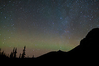 Faint aurora borealis and a star filled sky over the Brooks Range, Arctic, Alaska.